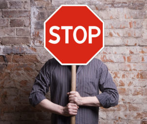 man holds a stop sign in front of his face