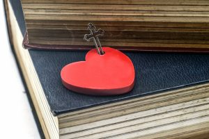 Red heart with cross and bible book